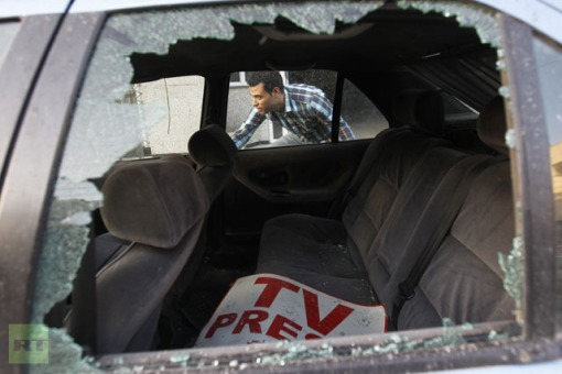 A Palestinian journalist inspects his work car in Gaza City